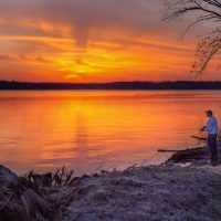 Fisherman on Mississippi River shorline above Hamilton, IL at sunset